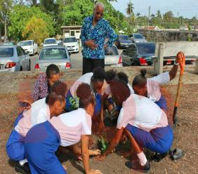 Fifth year students planting a tree as IT Coordinator, eronica Lovell-Grandison (kneeling) and Principal Dr. Yvette Mayers.