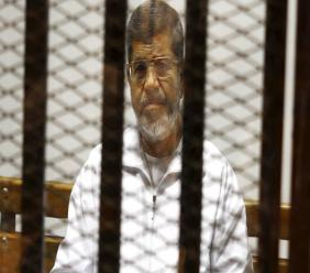 In this May 8, 2014 file photo, Egypt's ousted Islamist President Mohammed Morsi sits in a defendant cage in the Police Academy courthouse in Cairo, Egypt. Morsi was elected president in 2012 in the country's first free elections following the ouster the year before of longtime leader Hosni Mubarak. (AP Photo/Tarek el-Gabbas, File)