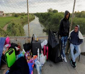 In this Nov. 2, 2018, file photo, Yenly Morales,left, and Yenly Herrera, right, immigrants from Cuba seeking asylum in the United States, wait on the Brownsville and Matamoros International Bridge in Matamoros, Mexico. (AP Photo/Eric Gay, File)