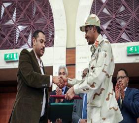 Gen. Mohammed Hamdan Dagalo, right, and Sudan's pro-democracy movement leader Ahmad al-Rabiah shake hands after signing a power sharing document in Khartoum, Sudan, Wednesday, July 17, 2019. (AP Photo/Mahmoud Hjaj)