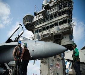 Photo: In this June 3, 2019 file photo, a pilot speaks to a crew member by an F/A-18 fighter jet on the deck of the USS Abraham Lincoln aircraft carrier in the Arabian Sea.  By Thursday, June 27, 2019, Iran says it will have over 300 kilograms of low-enriched uranium in its possession, which would mean it had broken out of the atomic accord. (AP Photo/Jon Gambrell, File)