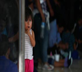 A migrant child looks at the camera while her parents wait at an immigration centre on the International Bridge 1, in Nuevo Laredo, Mexico, Tuesday, July 16, 2019. (AP Photo/Marco Ugarte)