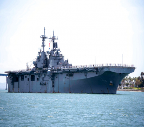"""In this May 1, 2019, photo provided by the U.S. Navy, the amphibious assault ship USS Boxer (LHD 4) transits the San Diego Bay in San Diego, Calif. President Donald Trump says the USS Boxer destroyed an Iranian drone in the Strait of Hormuz amid heightened tensions between the two countries. Trump says it's the latest """"hostile"""" action by Iran. (Mass Communication Specialist 2nd Class Jesse Monford/U.S. Navy via AP)"""