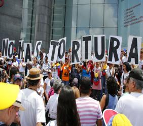 "People hold placards that spell out in Spanish: ""No more torture"" during an opposition protest against President Nicolas Maduro in Caracas, Venezuela, Friday July 5, 2019. (AP Photos/Leonardo Fernandez)"