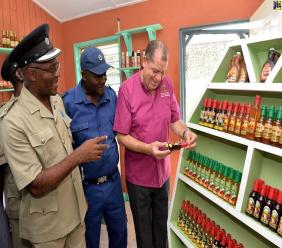 Minister of Industry, Commerce, Agriculture and Fisheries, Audley Shaw (right), reads the labels of one of the wines produced by inmates at the St. Catherine Adult Correctional Centre during a recent visit to the facility. From left are Superintendent of the facility, Herbert McFarlane; and Correctional Officer, Joel Lilly.