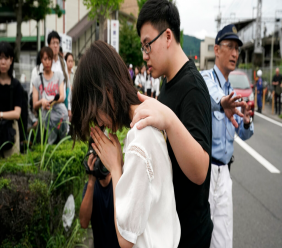 "A woman prays to honor the victims of Thursday's fire at the Kyoto Animation Studio building, Friday, July 19, 2019, in Kyoto, Japan. A man screaming ""You die!"" burst into the animation studio in Kyoto, doused it with a flammable liquid and set it on fire Thursday, killing dozens of people in the attack that shocked the country and brought an outpouring of grief from anime fans. (AP Photo/Jae C. Hong)"