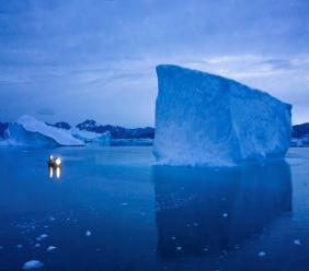 """In this Aug. 15, 2019, photo, a boat navigates at night next to icebergs in eastern Greenland. U.S. President Trump announced his decision to postpone a visit to Denmark by tweet on Tuesday Aug. 20, 2019, after Danish Prime Minister Mette Frederiksen dismissed the notion of selling Greenland to the U.S. as """"an absurd discussion."""" (AP Photo/Felipe Dana)"""