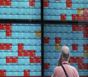 A man looks at an electronic stock board showing Japan's Nikkei 225 index at a securities firm in Tokyo Friday, Aug. 16, 2019. (AP Photo/Eugene Hoshiko)