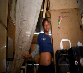 In this photo taken Aug. 5, 2019, 14-year-old Rosibeth Vargas, who is seven months pregnant, stands in her home where she lives with her parents, 18-year-old sister and nephew, in the Tablitas area of the Caucaguita neighborhood on the outskirts of Caracas, Venezuela. (AP Photo/Ariana Cubillos)