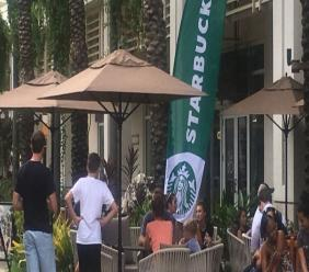 A large group congregating in patient anticipation for Starbucks to open its doors.