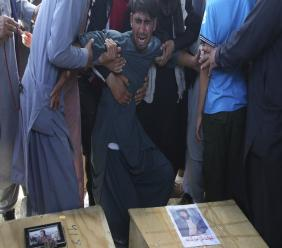 A relative wails near the coffins of victims of the Dubai City wedding hall bombing during a mass funeral in Kabul, Afghanistan, Sunday, Aug.18, 2019. The deadly bombing at the wedding in Afghanistan's capital late Saturday that killed dozens of people was a stark reminder that the war-weary country faces daily threats not only from the long-established Taliban but also from a brutal local affiliate of the Islamic State group, which claimed responsibility for the attack. (AP Photo/Rafiq Maqbool)