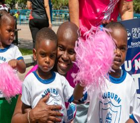 Breast cancer survivor Hygena Reid enjoys a moment with children from the Auburn Basic School during the ICWI Pink Dash at The Emancipation Park on Friday, October 11,2019. The Pink Dash was staged as a unique and exciting preparatory exercise ahead of the ICWI Pink Run set for Sunday, October 27.