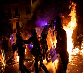 Policemen run as a police van drives over a burning barricade during clashes between protestors and police in Barcelona, Spain, October 16, 2019. (AP Photo/Bernat Armangue)