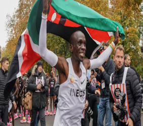 Eliud Kipchoge celebrates with the Kenyan flag after breaking the historic two hour barrier for a marathon in Vienna, Saturday, Oct. 12, 2019.  (Jed Leicester/The INEOS 1:59 Challenge via AP)