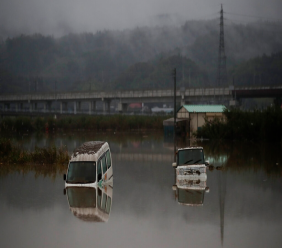 Two vehicles are submerged in floodwaters Monday, Oct. 14, 2019, in Hoyasu, Japan. Rescue crews in Japan dug through mudslides and searched near swollen rivers Monday as they looked for those missing from a typhoon that left as many as 36 dead and caused serious damage in central and northern Japan. (AP Photo/Jae C. Hong)
