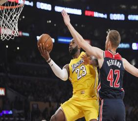 Los Angeles Lakers forward LeBron James, left, shoots as Washington Wizards forward Davis Bertans defends during the first half of an NBA basketball game Friday, Nov. 29, 2019, in Los Angeles. (AP Photo/Mark J. Terrill).