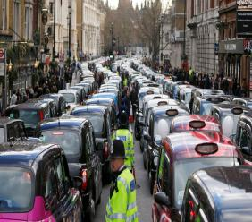 In this Wednesday, Feb. 10, 2016 file photo, London taxis block the roads during a protest in central London, concerned with unfair competition from services such as Uber. (AP Photo/Frank Augstein, File)