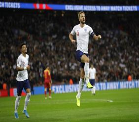 England's Harry Kane, right, celebrates scoring the fifth goal during the Euro 2020 group A qualifying football match against Montenegro at Wembley stadium in London, Thursday, Nov. 14, 2019. (AP Photo/Kirsty Wigglesworth).