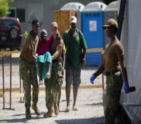 US soldiers carry an elderly Haitian woman to see a US military doctor from the US Navy hospital ship USNS Comfort anchored off Port-au-Prince, Haiti, November 8, 2019. (AP Photo/Dieu Nalio Chery)