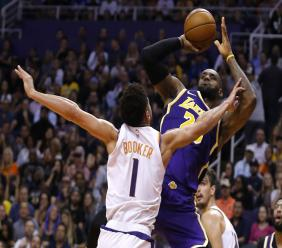 Los Angeles Lakers forward LeBron James gets fouled by Phoenix Suns guard Devin Booker (1) in the first half during an NBA basketball game, Tuesday, Nov. 12, 2019, in Phoenix. (AP Photo/Rick Scuteri).