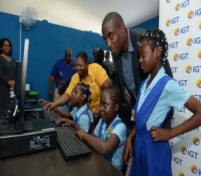 IGT team member, Rohan Williams, Technology Manager (second right) and Community Relations Officer at the Jamaica Broilers Group, Cyrine Cargill (third right) assist the children in using the computers donated by IGT Jamaica. Looking on is IGT General Manager, Debbie Green (far left).