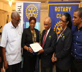 Christopher Samuda (3rd left), President of the Jamaica Paralympic Association admires the Paul Harris Fellow recognition certificate he received from the Rotary Club of St Andrew North. Looking on are: Joscelyn Jolly, H. Annmarie Curtis, Suzanne Harris-Henry (2nd right) and Dr Rory Dixon (right), Director of the Jamaica Paralympic Association.
