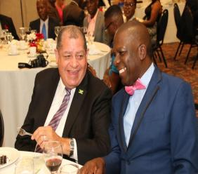 President of the Jamaica Coffee Exporters Association, Norman Grant shares a laugh with Minister of Industry, Commerce, Agriculture and Fisheries Audley Shaw at the annual banquet of the JCEA on Saturday, December 7.
