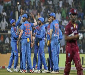 Indian cricketers celebrate the dismissal of West Indies' Lendl Simmons during the third Twenty20 international cricket match between India and West Indies in Mumbai, India, Wednesday, Dec. 11, 2019. (AP Photo/Rafiq Maqbool)