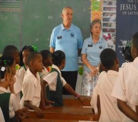 Elder David Nish (left) and Sister Theresa Nish speaking to the students