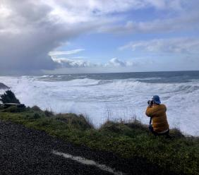 In this January 11, 2020 photo a man photographs waves crashing onto the cliffs at Rodea Point in Lincoln County, Ore. during an extreme high tide that coincided with a big winter storm. Amateur scientists are whipping out their smartphones to document the effects of extreme high tides on shore lines from the United States to New Zealand, and by doing so are helping better predict what rising sea levels due to climate change will mean for coastal communities around the world. (AP Photo/Gillian Flaccus)