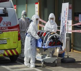 In this Wednesday, Feb. 19, 2020, photo, medial workers wearing protective gears move a patient suspected of contracting the new coronavirus from an ambulance to the Kyungpook National University Hospital in Daegu, South Korea. (Kim Jong-un/Yonhap via AP)