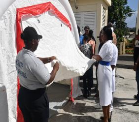 Photo via Facebook, SVG Ministry of Health, Wellness and the Environment: Staff at Milton Cato Memorial Hospital being retrained to use a mobile isolation system