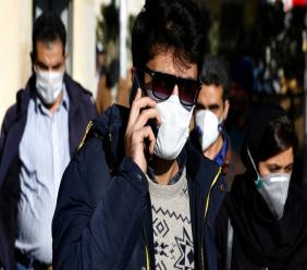 In this Monday, March 2, 2020 file photo, a man wearing a face mask, to help protect against the new coronavirus, speaks on his cellphone in downtown Tehran, Iran. (AP Photo Vahid Salemi, File)