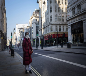 """A woman walks down the Strand during """"rush hour"""" in Westminster, London, Thursday March 26, 2020. The new coronavirus causes mild or moderate symptoms for most people, but for some, especially older adults and people with existing health problems, it can cause more severe illness or death. (Victoria Jones/PA via AP)"""