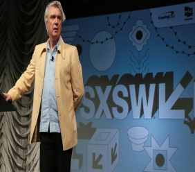 """In this March 13, 2019 file photo, David Byrne takes part in the """"Reasons To Be Cheerful"""" featured session during the South by Southwest Music Festival in Austin, Texas. Austin city officials have canceled the South by Southwest arts and technology festival. Mayor Steve Adler announced a local emergency that effectively canceled the annual event. (Photo by Jack Plunkett/Invision/AP, File)"""