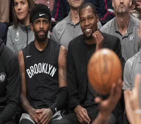 In this Nov. 1, 2019, file photo, Brooklyn Nets' Kyrie Irving, left, and Kevin Durant watch the game action from the bench during the second half of an NBA basketball game against the Houston Rockets in New York.