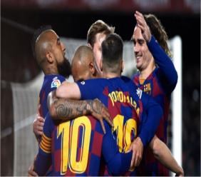 Barcelona players celebrate  Lionel Messi's opening goal against Real Sociedad.