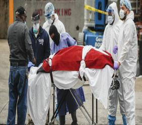 A body wrapped in plastic that was unloaded from a refrigerated truck is handled by medical workers wearing personal protective equipment due to COVID-19 concerns, Tuesday, March 31, 2020, at Brooklyn Hospital Center in Brooklyn borough of New York. (AP Photo/John Minchillo)