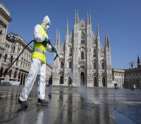 A worker sprays disinfectant to sanitize Duomo square, as the city main landmark, the gothic cathedral, stands out in background, in Milan, Italy, Tuesday, March 31, 2020. The new coronavirus causes mild or moderate symptoms for most people, but for some, especially older adults and people with existing health problems, it can cause more severe illness or death. (AP Photo/Luca Bruno)
