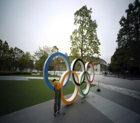 In this Tuesday, April 21, 2020, file photo, a child plays at the Olympic rings in front of the New National Stadium in Tokyo. A staff member of the Tokyo Olympic organising committee has tested positive for COVID-19, according to Tokyo organisers in a statement released on Wednesday. (AP Photo/Eugene Hoshiko, File).