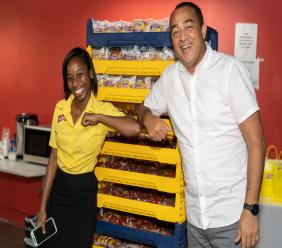 Russanette Dennis, Marketing Assistant of Consolidated Bakeries shares the elbow greeting with Minister of Health Dr Tufton during the recent handover.