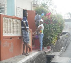 Customers outside a small shop in Laborie waiting on their turn to be served