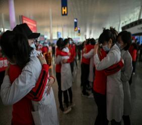 En rouge, le personnel médical de la province du Jilin embrasse celui de Wuhan lors d'une cérémonie avant de partir alors que l'aéroport de Tianhe est rouvert à Wuhan en Chine le 8 avril 2020