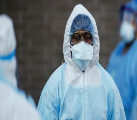 A medical worker wearing personal protective equipment pauses after wheeling a body to a refrigerated trailer serving as a makeshift morgue at Wyckoff Heights Medical Center, Monday, April 6, 2020, in the Brooklyn borough of New York. (AP Photo/John Minchillo)