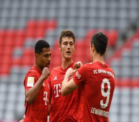 Munich's Benjamin Pavard, centre, Serge Gnabry, left, and Robert Lewandowski celebrate after scoring during the German Bundesliga football match between FC Bayern Munich and Fortuna Duesseldorf in Munich, Germany, Saturday, May 30, 2020. Because of the coronavirus outbreak all football matches of the German Bundesliga take place without spectators. (Christof Stache/Pool via AP).