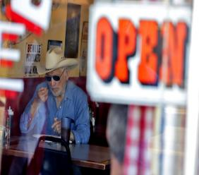 A customer eats inside the Horseshoe Cafe Friday, May 1, 2020, in Wickenburg, Arizona. (AP Photo/Matt York)