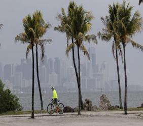 FILE - In this May 15, 2020, photo, the Miami skyline is shrouded in clouds as a cyclist rides along Biscayne Bay at Matheson Hammock Park, in Miami. National Oceanic and Atmospheric Administration's Climate Prediction Center, said Thursday, May 21, 2020, that six to 10 of the storms could develop into hurricanes, with winds of at least 74 mph. They're also predicting that three to six of those could develop into major hurricanes. (AP Photo/Lynne Sladky, File)
