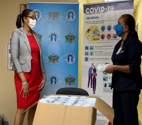 Margaret Monplaisir (right), CEO of St Lucia Distillers, presents masks to Saint Lucia's Chief Medical Officer, Dr Sharon Belmar-George.