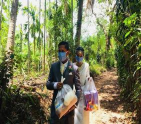 Darshana Kumara Wijenarayana and his bride Pawani Rasanga walk with packets of food to distribute in the small town of Malimbada, about 160 kilometres (99 miles) south of the capital Colombo. The Sri Lankan couple cancelled a wedding party and instead, shared their wedding day with some of their neediest neighbours who have been economically hit due to the lockdown following the new coronavirus COVID-19. (AP)