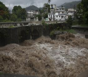 The swollen Los Esclavos River flows violently during tropical storm Amanda in Cuilapa, eastern Guatemala, Sunday, May 31, 2020. The first tropical storm of the Eastern Pacific season drenched parts of Central America on Sunday and officials in El Salvador said at least seven people had died in the flooding. (AP Photo/Moises Castillo).
